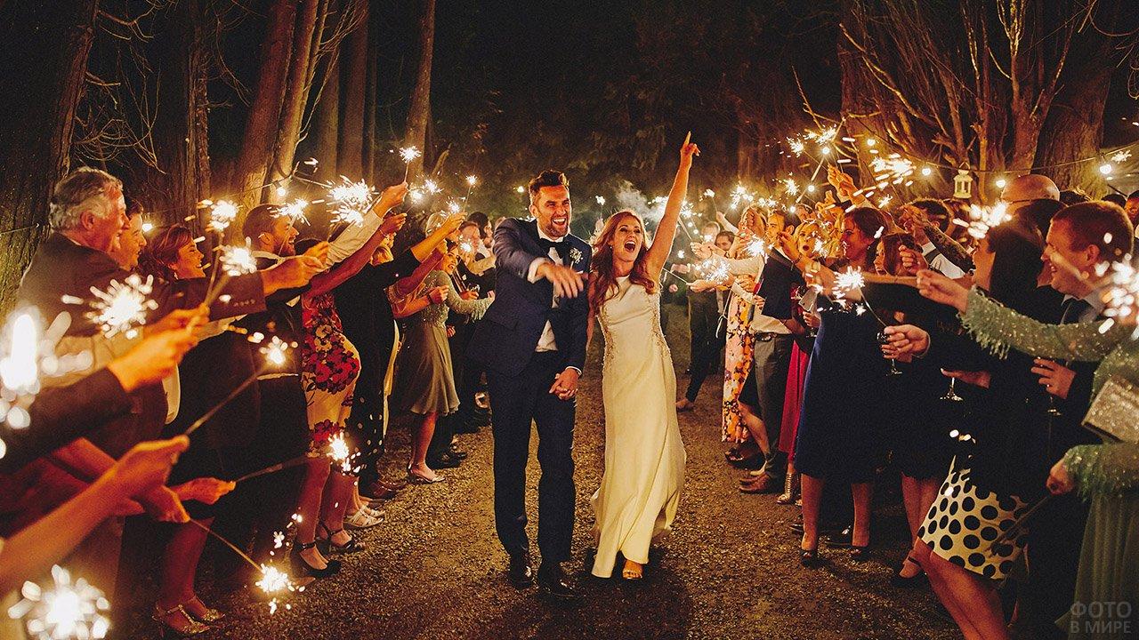 Счастливые молодожёны среди гостей с бенгальскими огнями