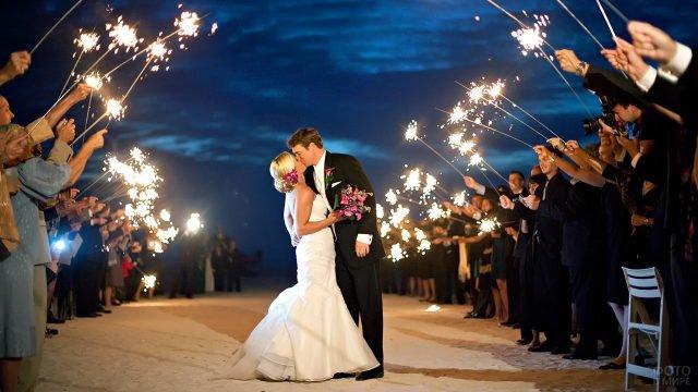 Свадебный поцелуй на пляже в кургу гостей с бенгальскими огнями