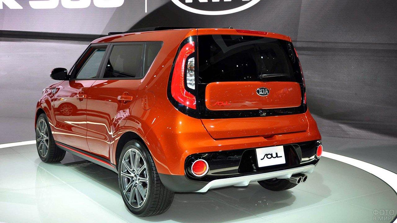 Киа Соул Турбо оранжевого цвета в динамичном ракурсе на стенде автосалона продаж