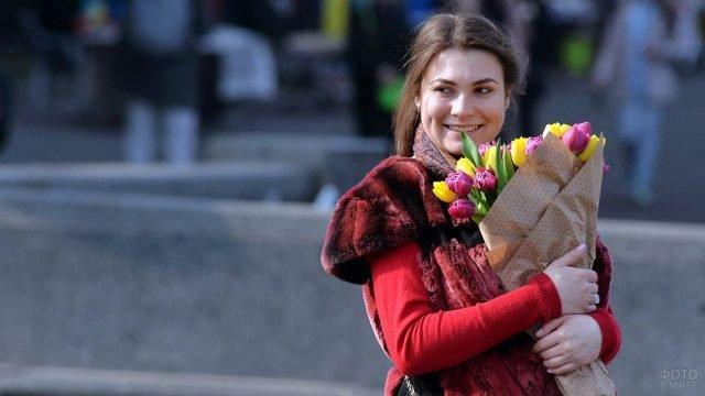 Девушка в красном с букетом тюльпанов на солнечной улице 8 марта