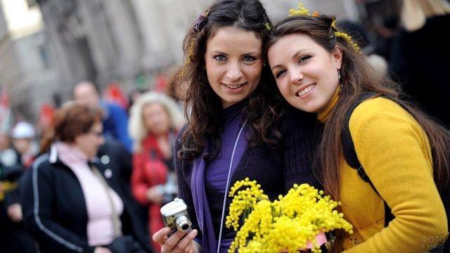 Девушки с букетом мимозы 8 марта на улице южного города