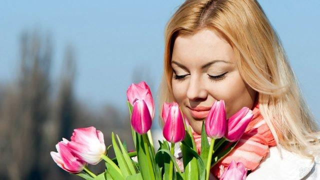 Довольная блондинка с букетом тюльпанов в солнечный день 8 марта