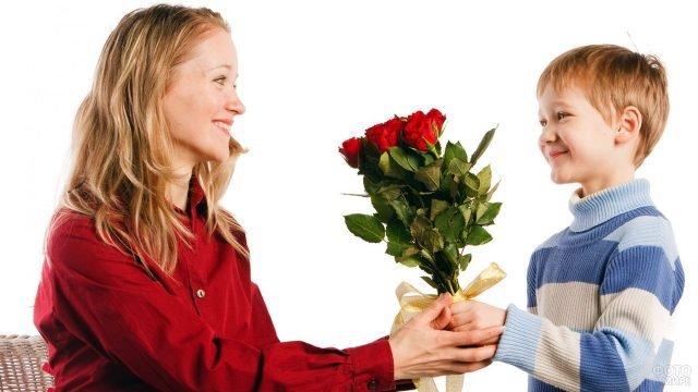 Мальчик дарит маме букет роз в международный женский день