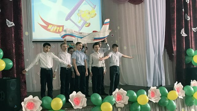Мальчишки выступают на сцене школы в день 8 марта