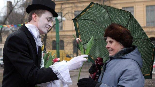 Мим дарит прохожей пенсионерке тюльпан 8 марта в Петербурге
