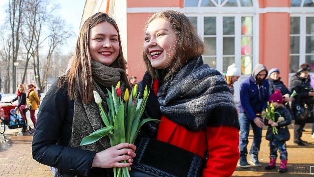 Счастливые девушки с тюльпанами 8 марта в московском парке