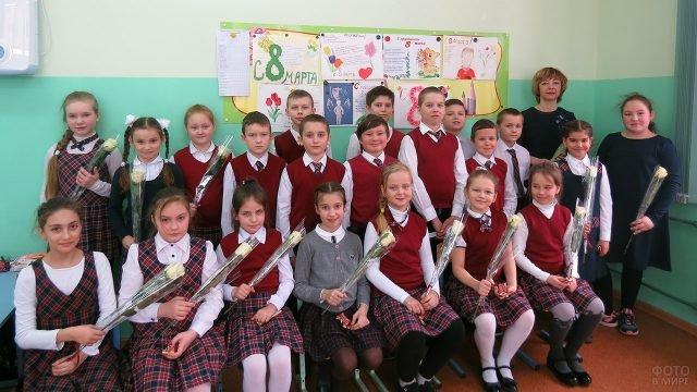 Школьницы с цветами от одноклассников в день 8 марта