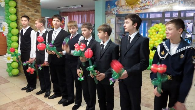 Школьники с надувными цветами для одноклассниц в честь 8 марта