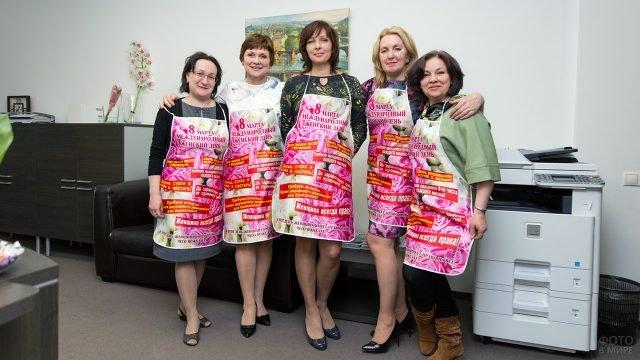 Сотрудницы офиса в подарочных фартуках-открытках от коллег в день 8 марта