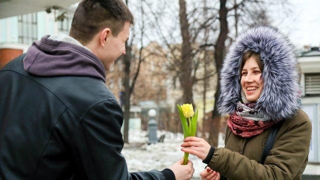 Улыбающиеся юноша и девушка с тюльпаном на улице 8 марта