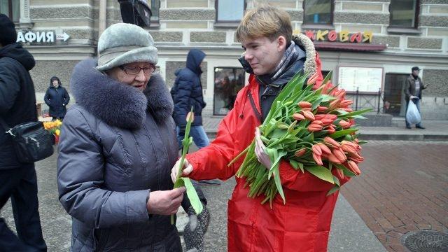 Волонтёр дарит пенсионерке красный тюльпан на улице города в женский день