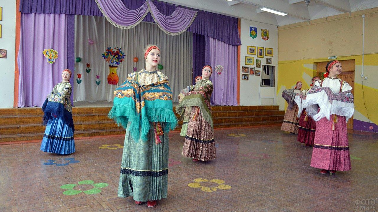 Выступление старшеклассниц в народных костюмах на концерте в честь 8 марта