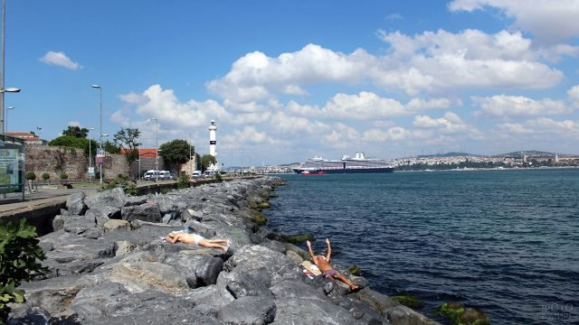 Люди загорают на камнях пляжа в центре Стамбула