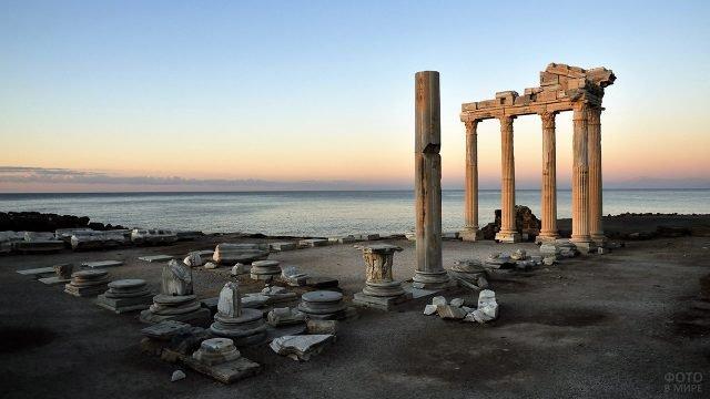 Руины города Сидэ на фоне заката над морем в Турции