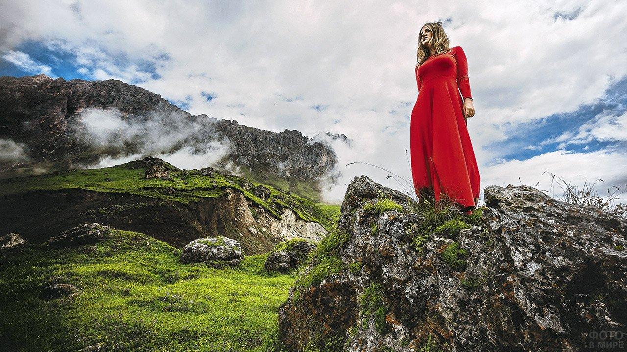 Блондинка в красном на фоне Кавказских гор в Ингушетии
