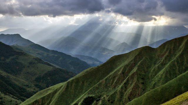 Лучи солнца падают сквозь тучи на перевал Медвежий крест в Грузии