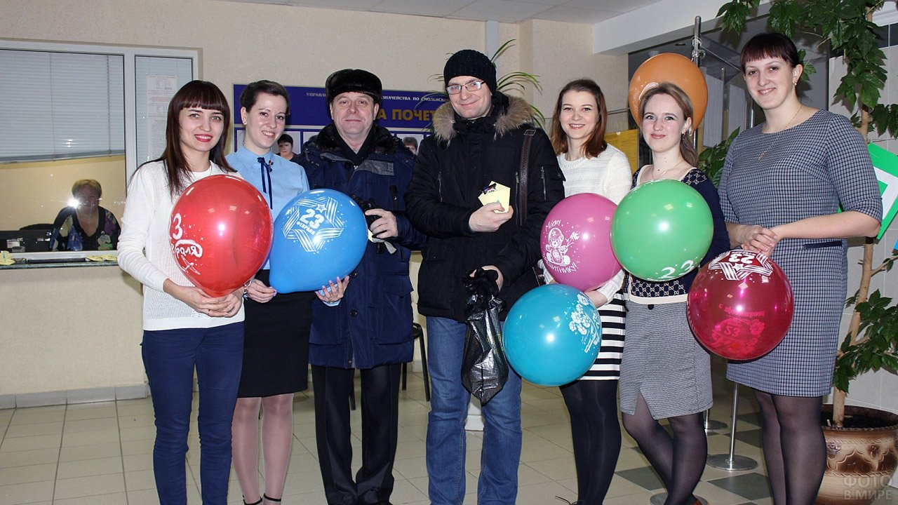 Девушки с яркими шариками поздравляют коллег с 23 февраля