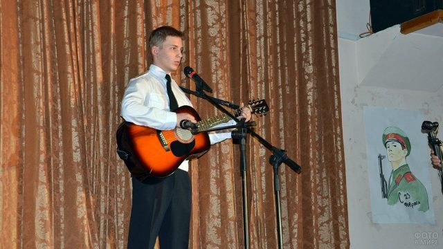 Юноша с гитарой выступает на концерте в честь 23 февраля на сцене колледжа