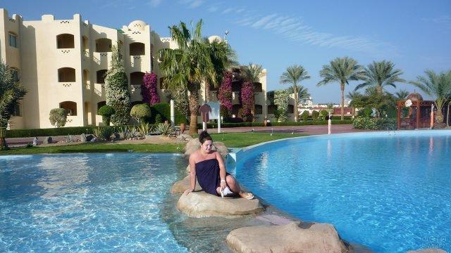 Корпулентная туристка на камнях в бассейне при отеле в Сома-Бей