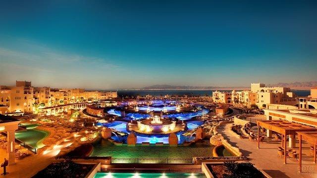 Освещённый басейн на территории отеля в Нувейбе