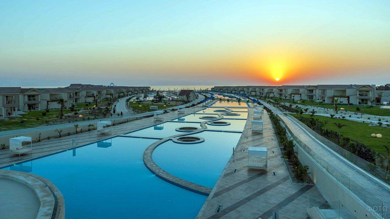 Территория отеля с бассейнами на фоне заката над морем в Марса-эль-Аламе