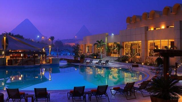 Вечерние огни роскошного спа-отеля в Каире с видом на пирамиды в Гизе