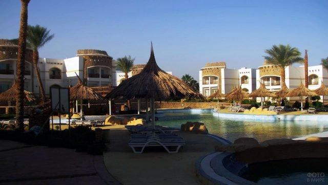 Зонтики из пальмовых листьев у бассейна при отеле в Шарм-Эль-Шейхе