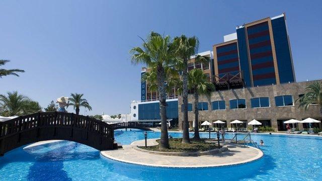 Остров с пальмами посреди бассейна при современном отеле в Сиде