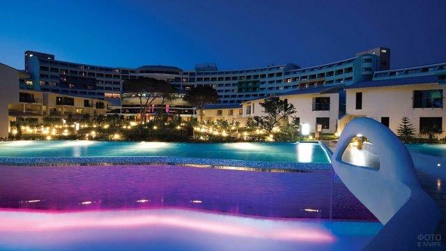 Современный турецкий отель с модерновым бассейном в вечерних огнях