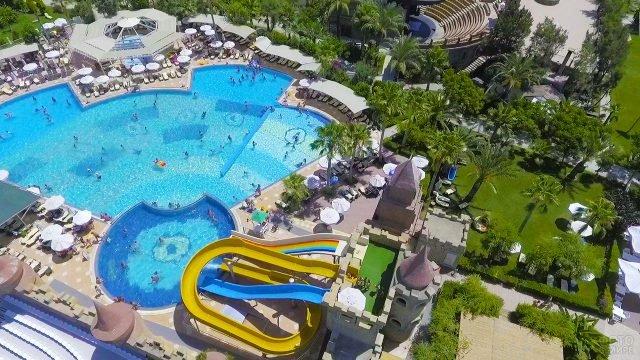 Вид сверху на бассейн с горками на территории отеля в городе Белек