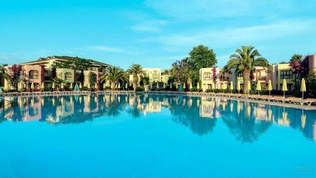 Зеркало бассейна в окружении пальм и бунгало отеля в Сиде