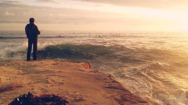 Человек с удочкой рыбачит в высоких волнах моря