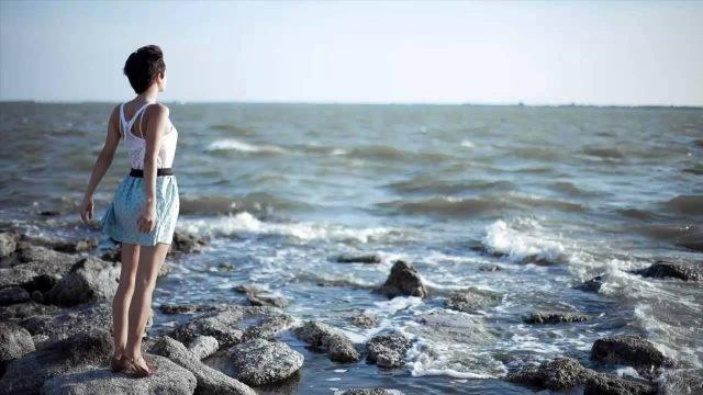 Девушка на берегу на фоне пенистых волн