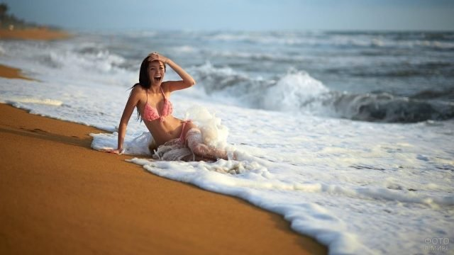 Девушка радуется в морской волне