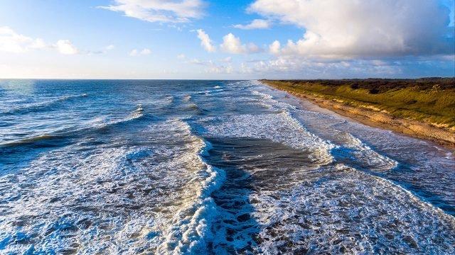 Дикий морской пляж во время прилива