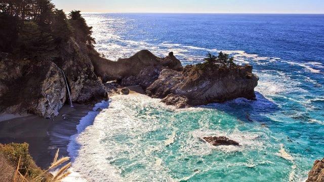 Дикий пляж с водопадом на скалистом морском берегу