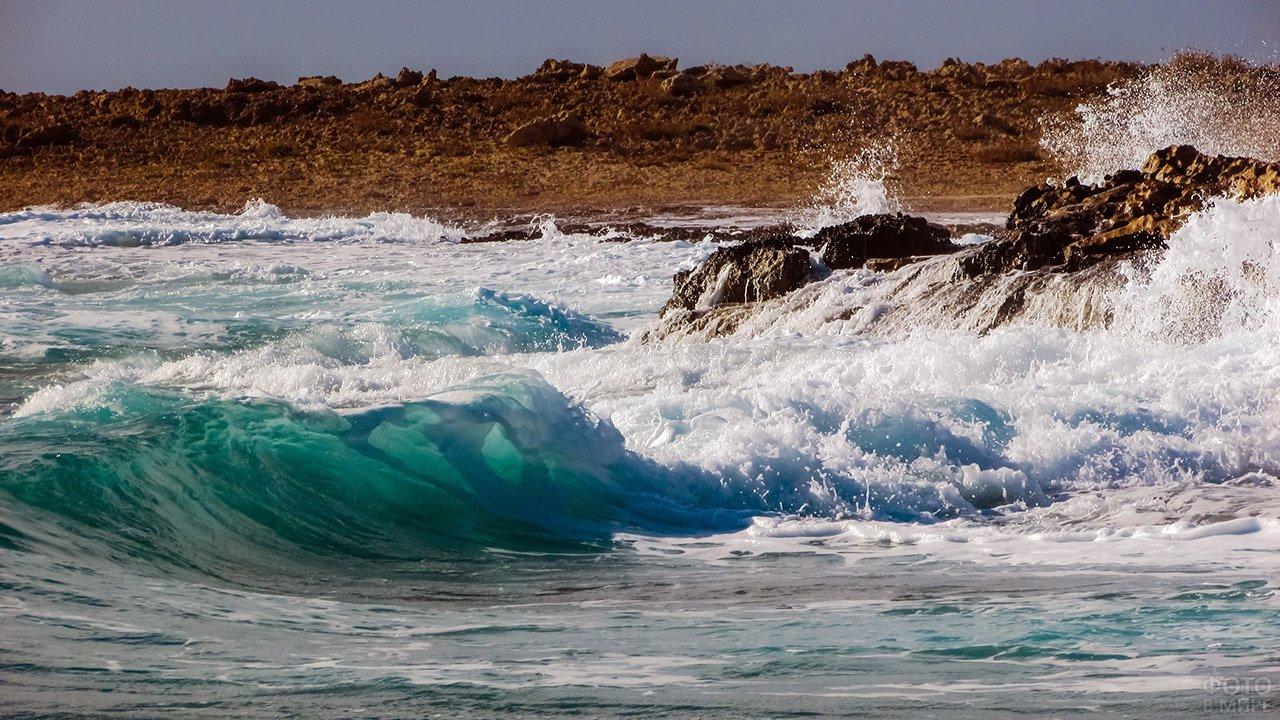 Каменистый морской берег в брызгах набегающих волн