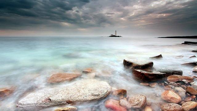 Камни на мелководье и маяк на горизонте в утреннем тумане над морем