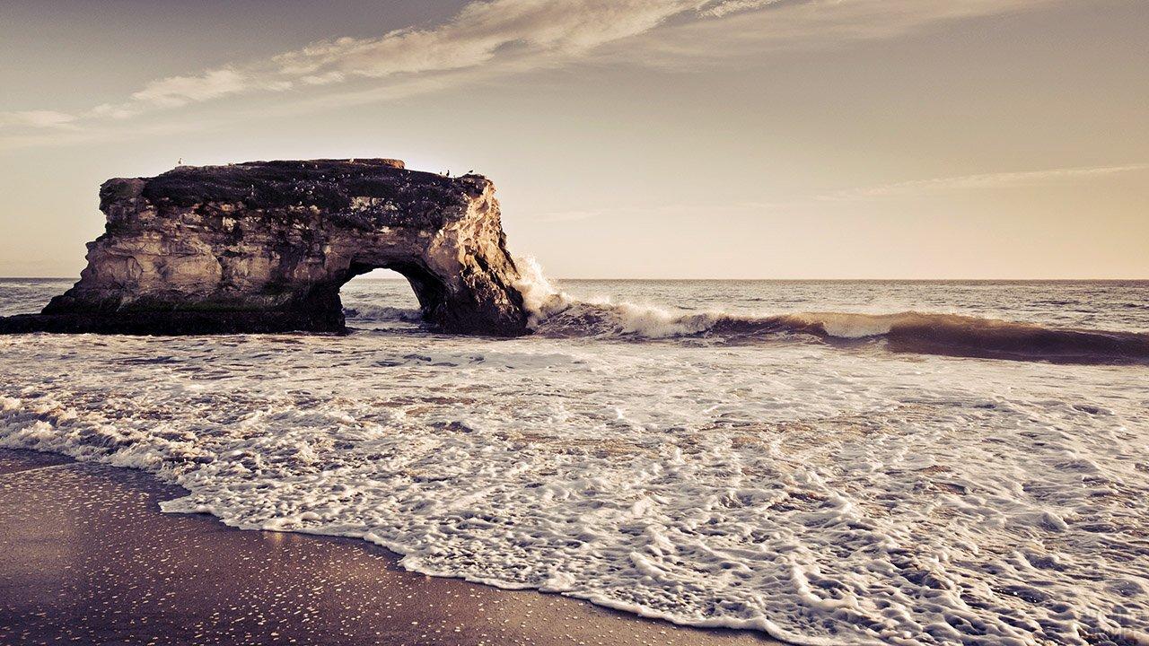 Морское побережье с живописной скалой на мелководье