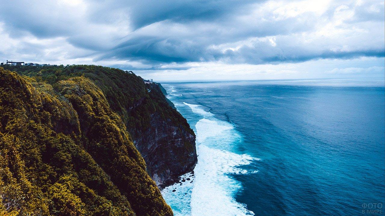Морской прибой у подножья скалы с высоты птичьего полёта