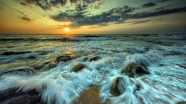 Набегающие на валуны морские волны в лучах заходящего солнца