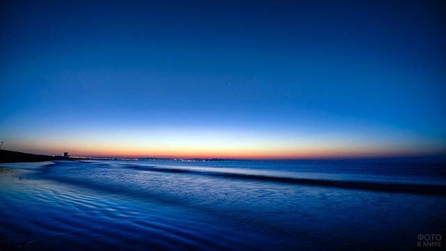 Ночное морское побережье и огни города на горизонте