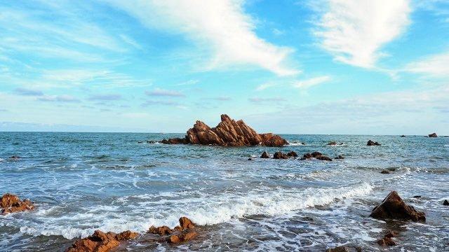Скалы на мелководье в волнах морского прибоя
