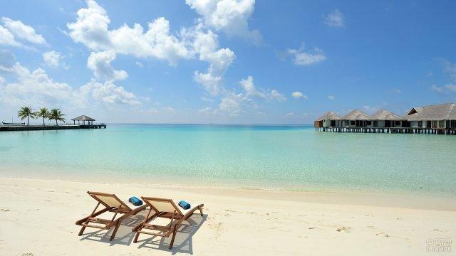 Тропический пляж с шезлонгами и бунгало у берега океана