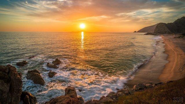 Заходящее солнце над диким пляжем