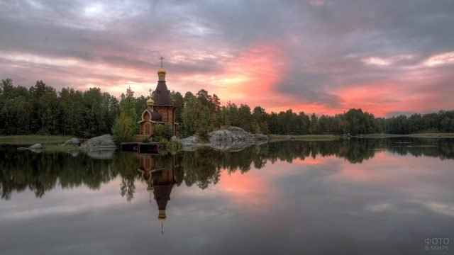 Деревянная церковь у озера на Золотом кольце в лучах заката