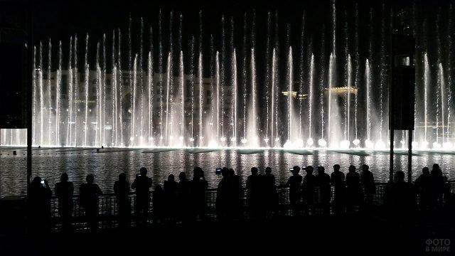 Силуэты зрителей ночного шоу фонтанов в Дубае