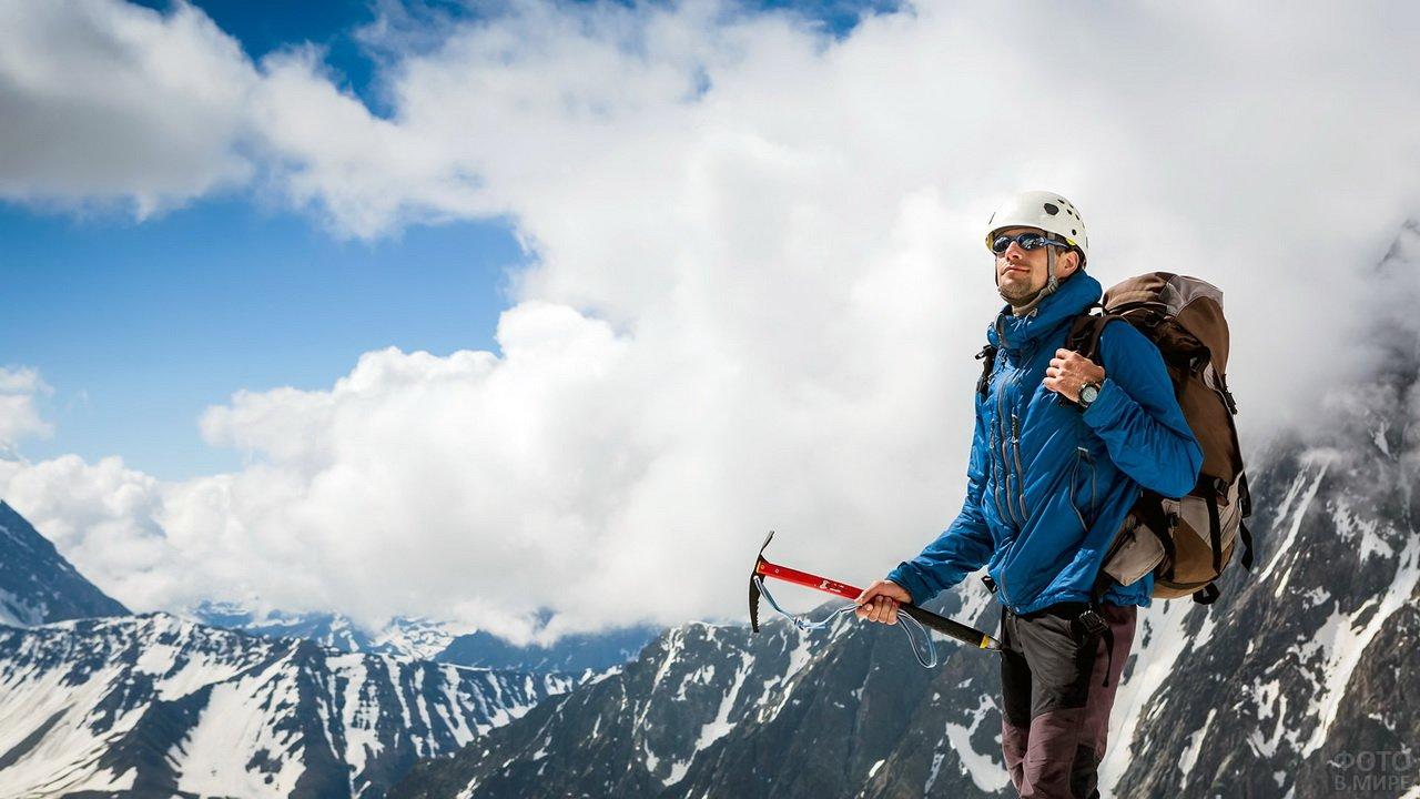 Альпинист с ледорубом на фоне гор