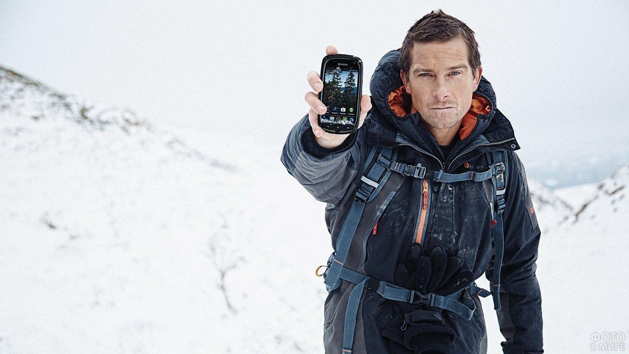 Беар Гриллс в горах со смартфоном в руках