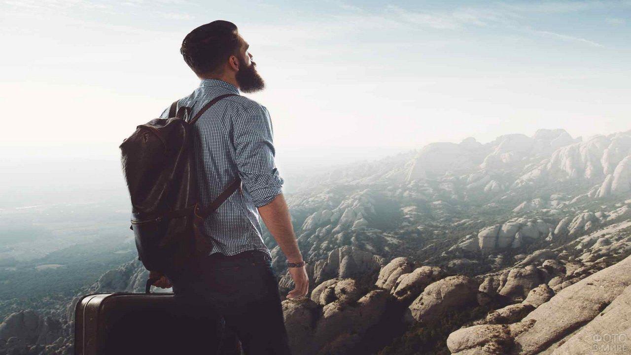 Бородатый путешественник с рюкзаком и чемоданом на фоне гор